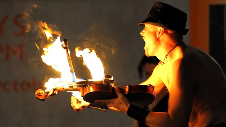 En  man i bart överkropp och hatt spelar på en brinnande fiol.