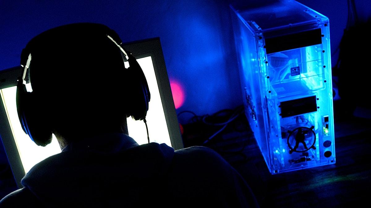 Siluetten av en dataspelare framför en dataskärm.