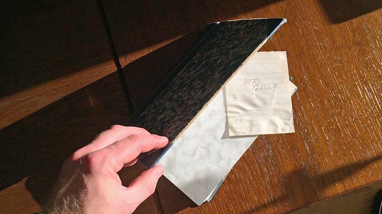 Hand öppnar gammal bok och där i ligger en anteckningslapp.