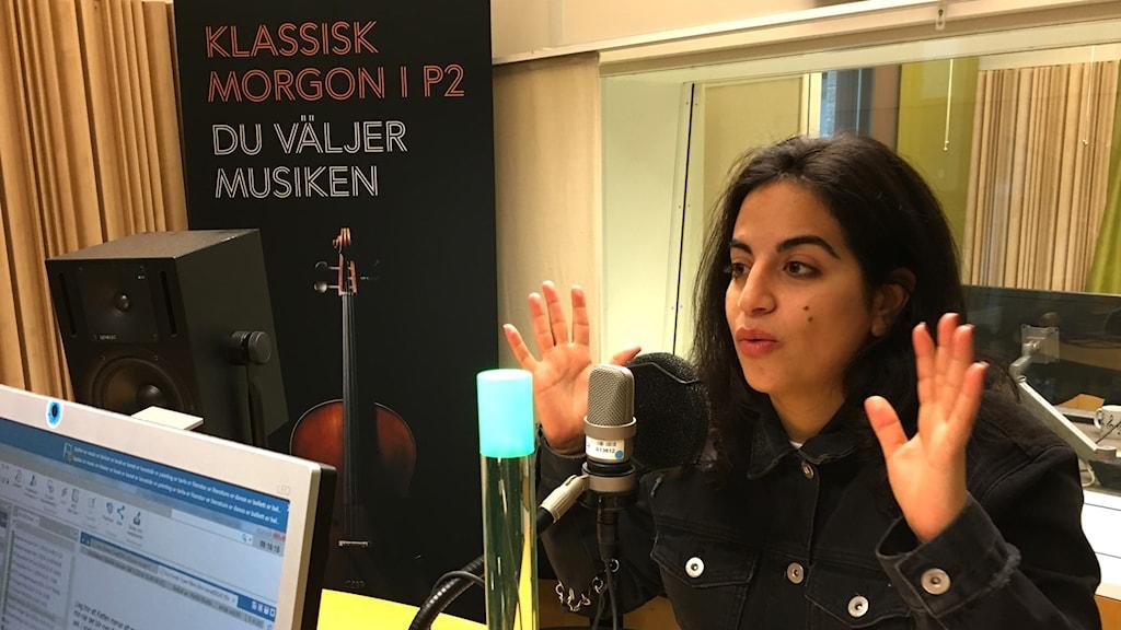 Maria Nohra lyfter båda sina händer i höjd med sitt ansikte när hon sitter i en radiostudio.