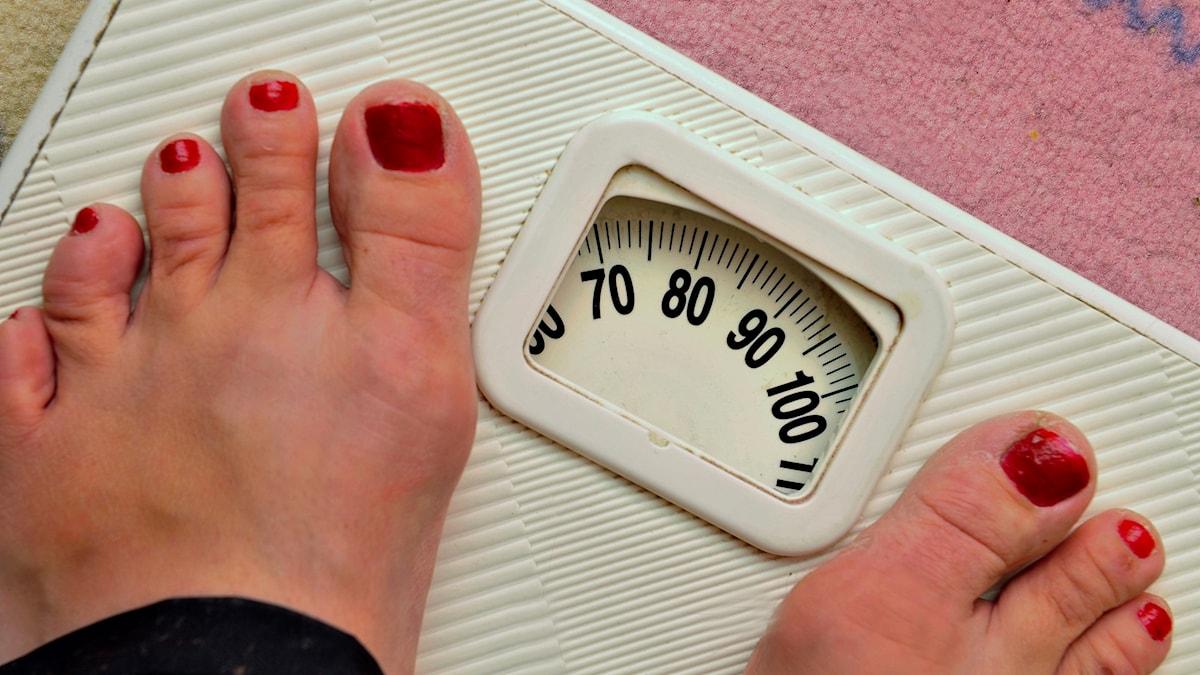 Ett par fötter med nagellack på tånaglarna står på en personvåg som visar drygt 80 kg.
