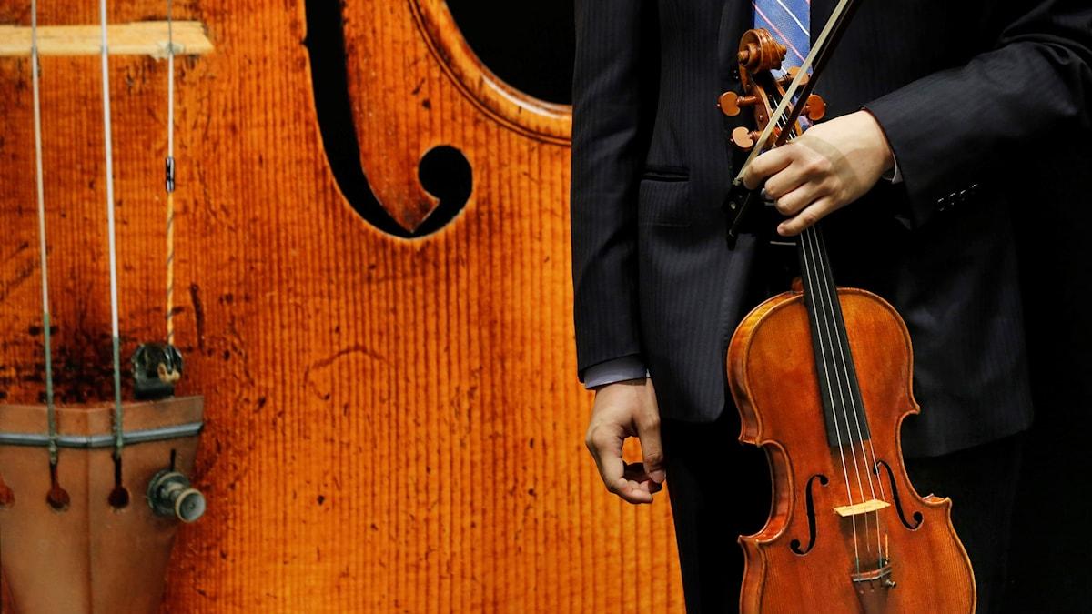 Kostymklädd man som håller en viola och en stråke framför sig.