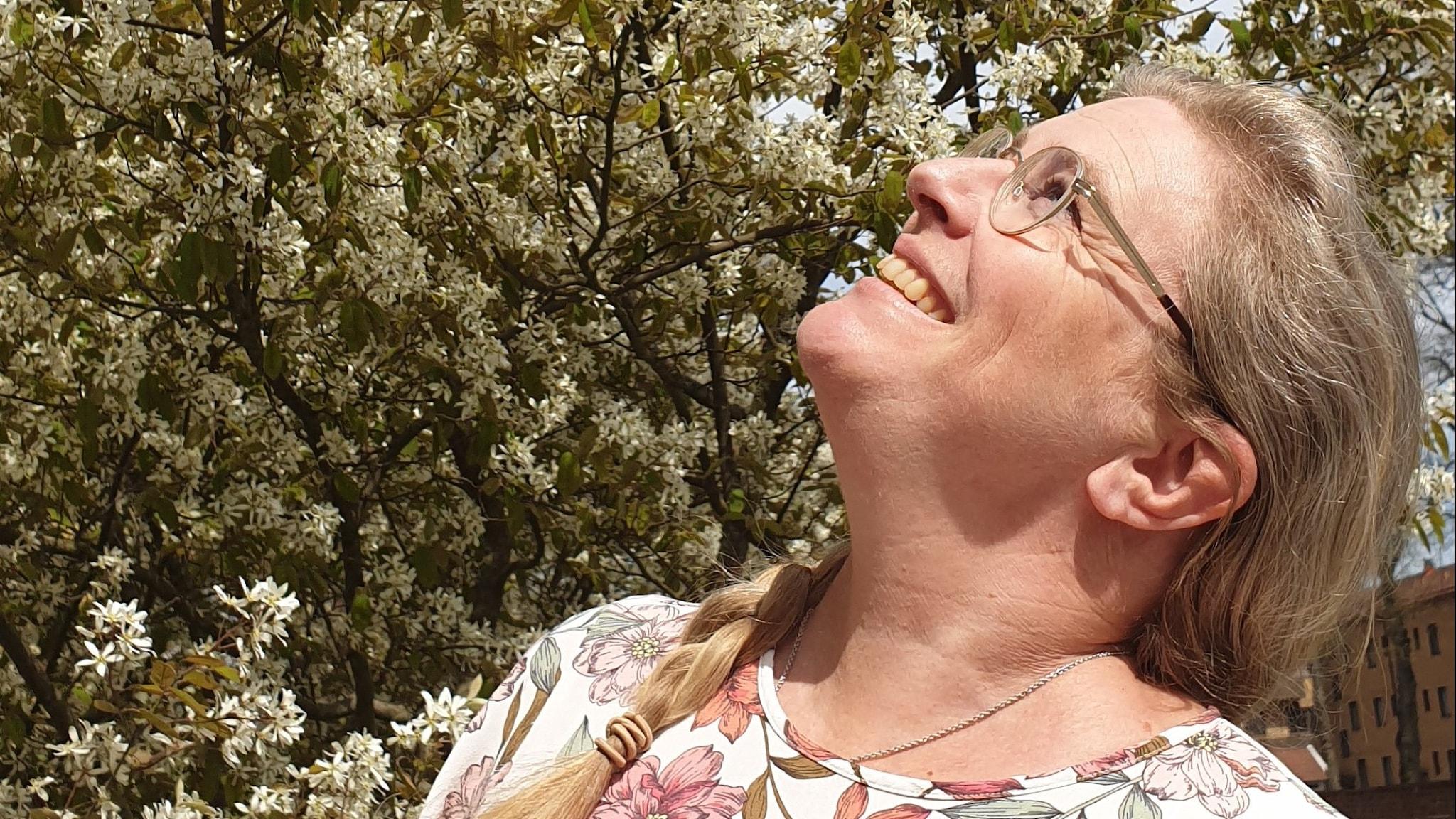 Pernilla Eskilsdotter till höger i bild, blickar snett upp mot himlen till vänster. I bakgrunden en buske med vita blommor. Solen skiner och Pernilla har e blommig tröja.