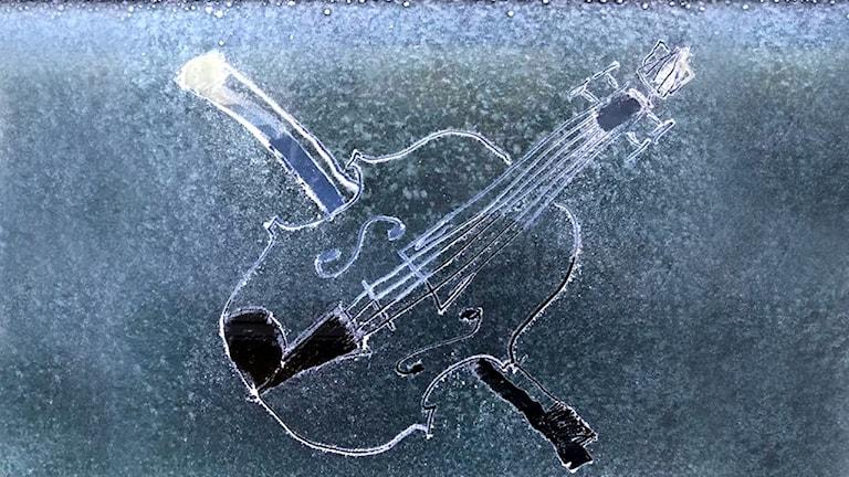 En fiol och en stråke utskrapad i frosten på en bilruta.