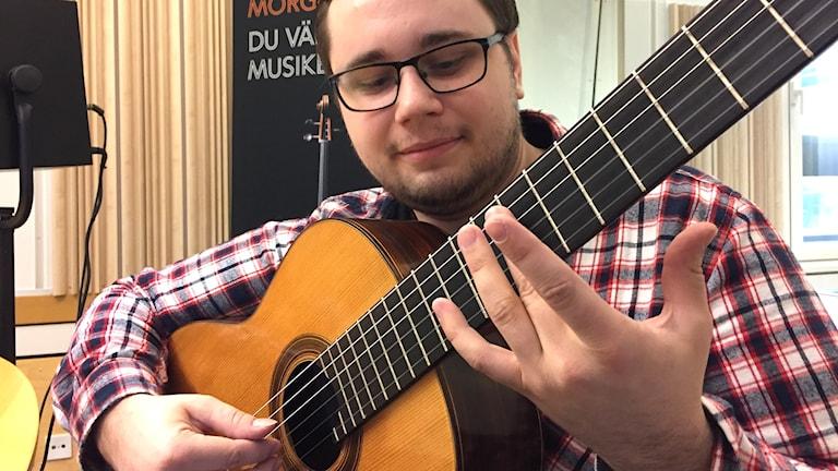 Gitarrläraren Emil Nordén visar hur man spelar en flageolett.