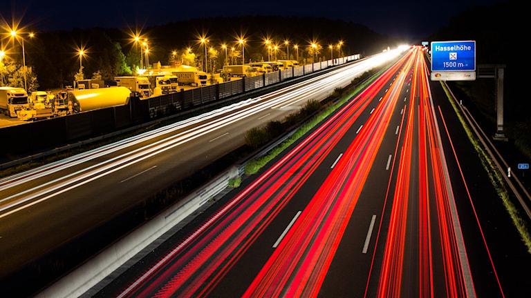 Billysena från fordonen som susar fram på Autobahn bildar långa streck längs med den mörka vägbanan.