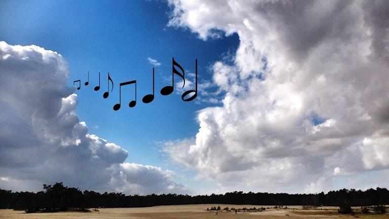 Noter kommer fram bakom ett moln på himlen.
