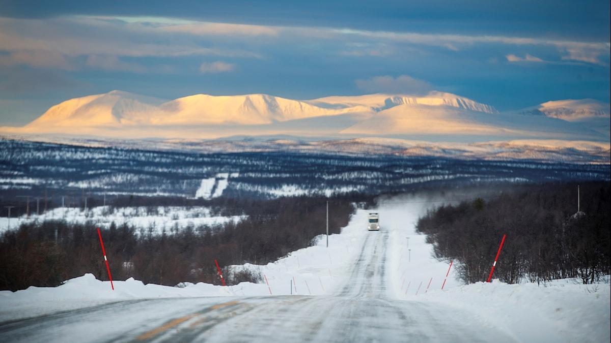En lastbil kommer körande långt bort i fjärran på en vinterväg med soldränkta fjälltoppar i bakgrunden.