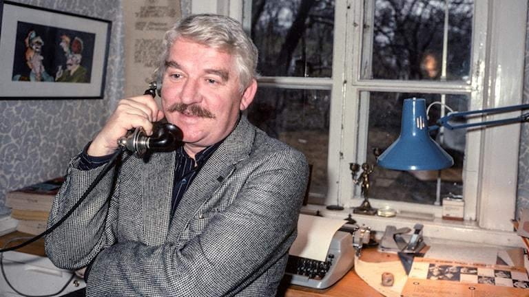 Hasse Alfredson med ryggen vänd mot sitt skrivbord pratar i en gammaldags telefonlur.
