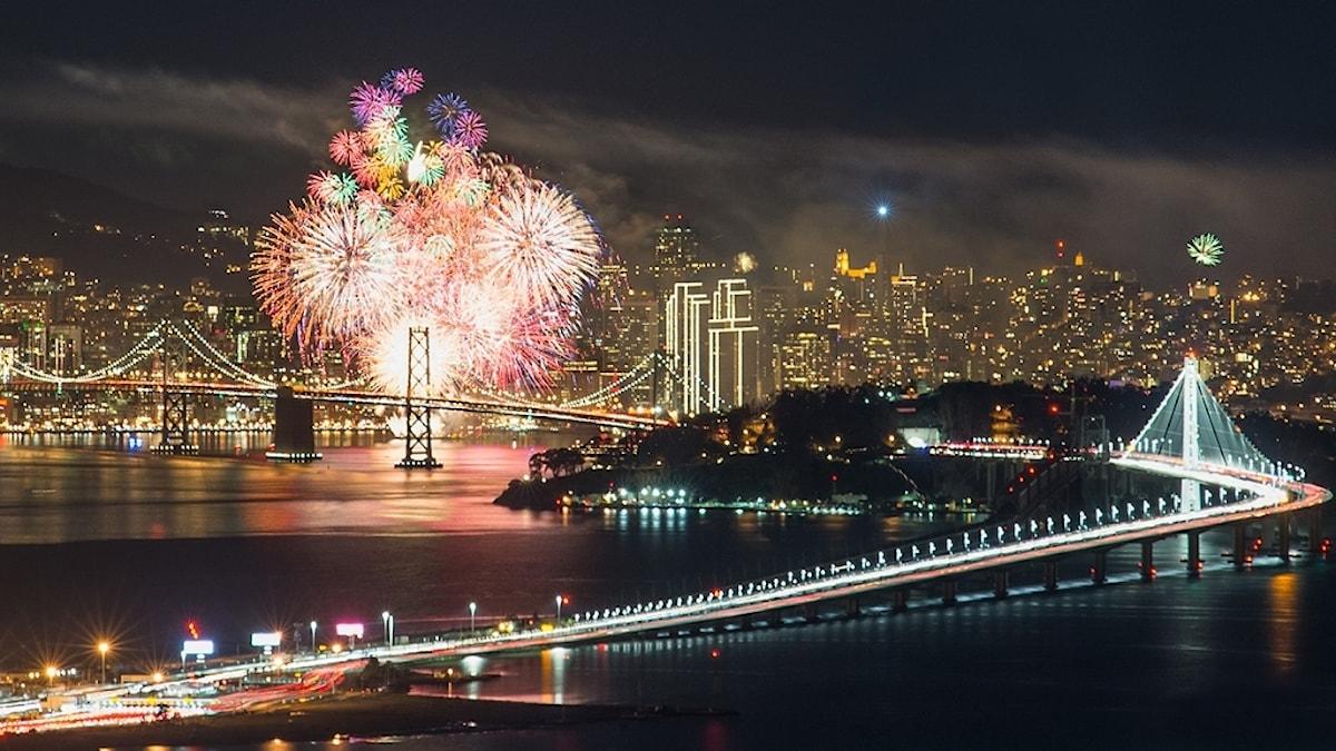 Nyårsfyrverkerier över en storstad med skyskrapor och upplysta broar över vatten.