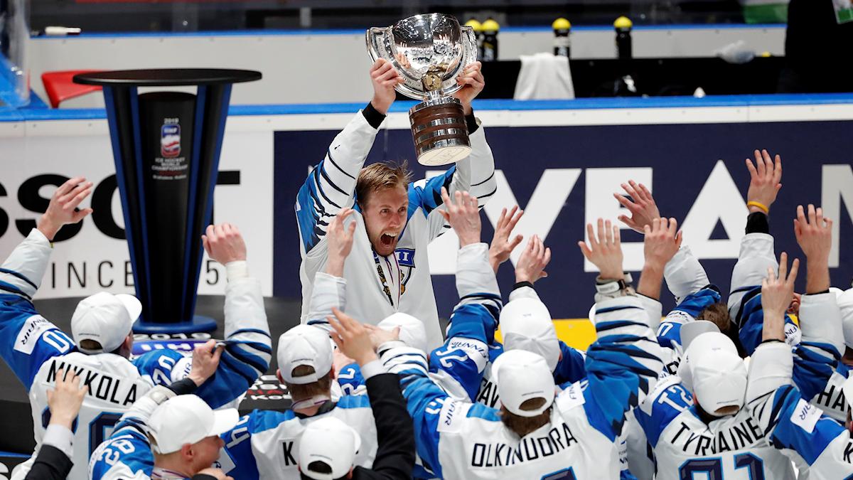 Marko Anttila lyfter VM-bucklan och de finländska lagkamraterna jublar.