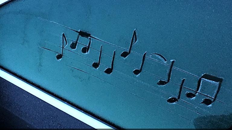 Noter som är framskrapade i frosten på en bilruta.