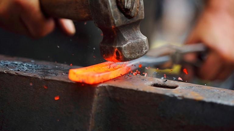 En hammare slår mot en glödande järnbit.