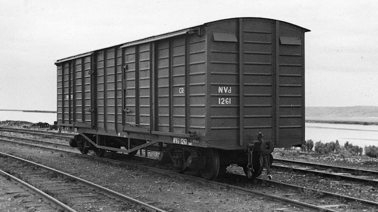 En gammaldags godsvagn som står stilla på järnvägsrälsen.