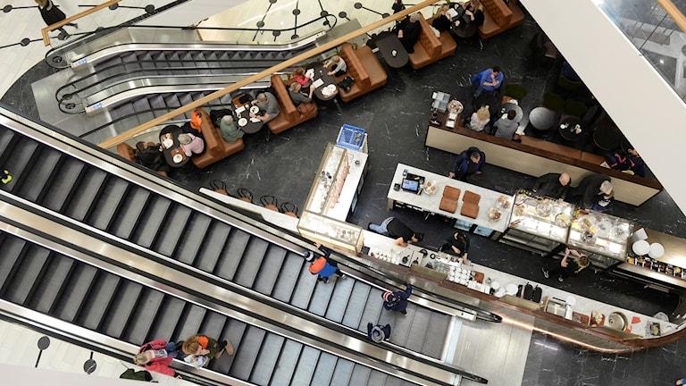 Ett café mellan rulltrapporna sett från ovan i en galleria.