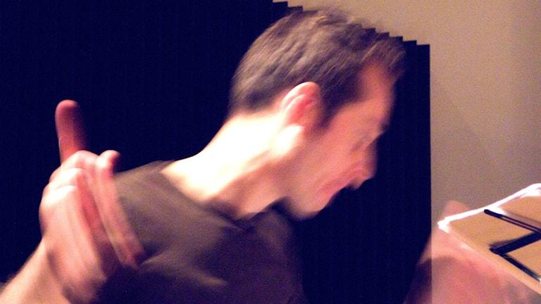 En suddig bild på man som dirigerar och viftar med armarna.