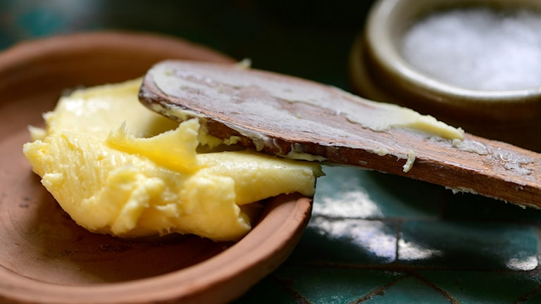 Hemkärnat smör på ett fat och en smörkniv i trä.