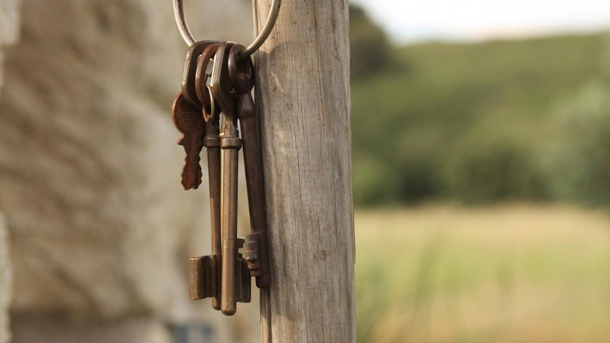 En nyckelknippa med gamla nycklar hänger på en trästolpe.