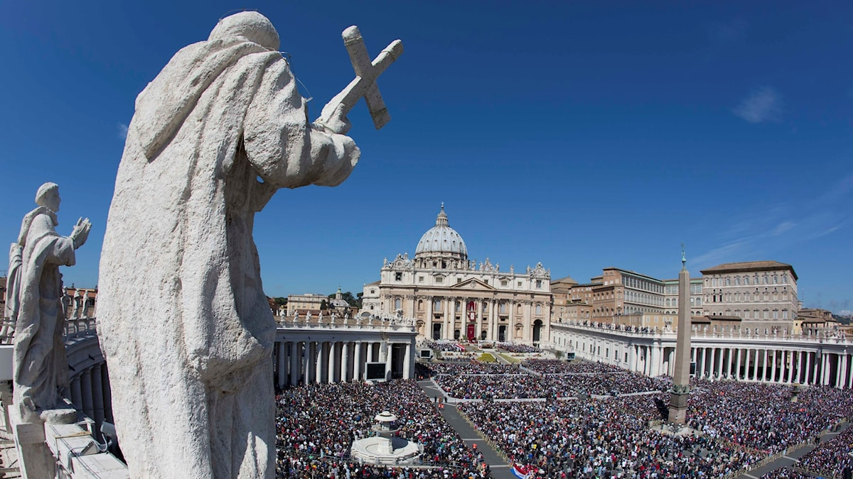 En staty med ett krucifix tittar ut över Petersplatsen i Vatikanstaten i Rom.
