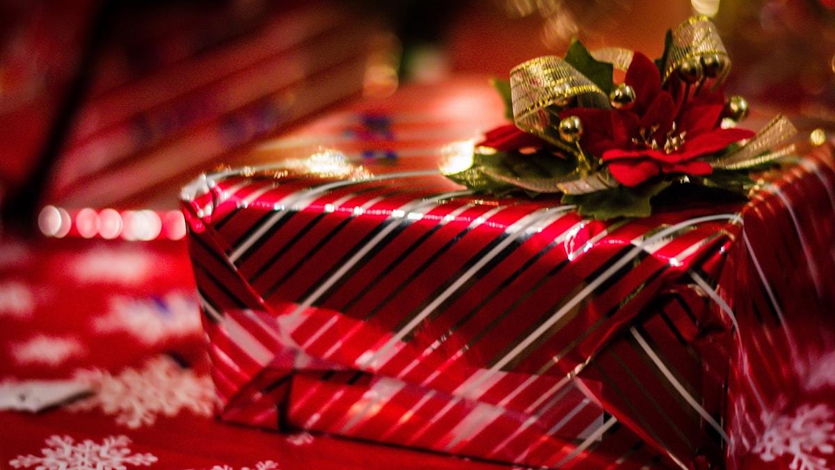 Julklapp inslagen i glänsande papper med en guldrosett på toppen.