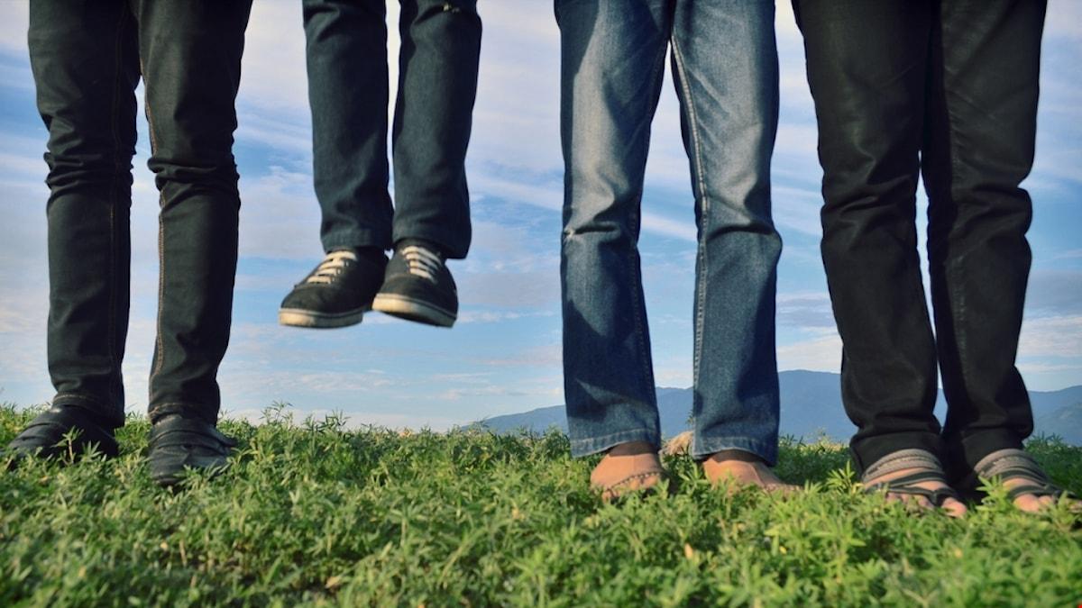 """Fyra par jeansklädda ben står bredvid varandra, varav ett par """"svävar"""" i luften."""
