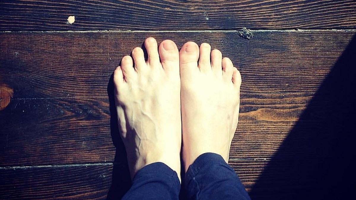 Två barfotade fötter på ett trägolv.