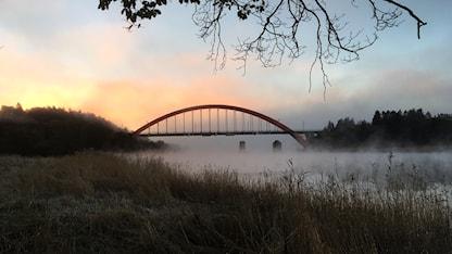En välvd bro går över ett dimmigt vattendrag.