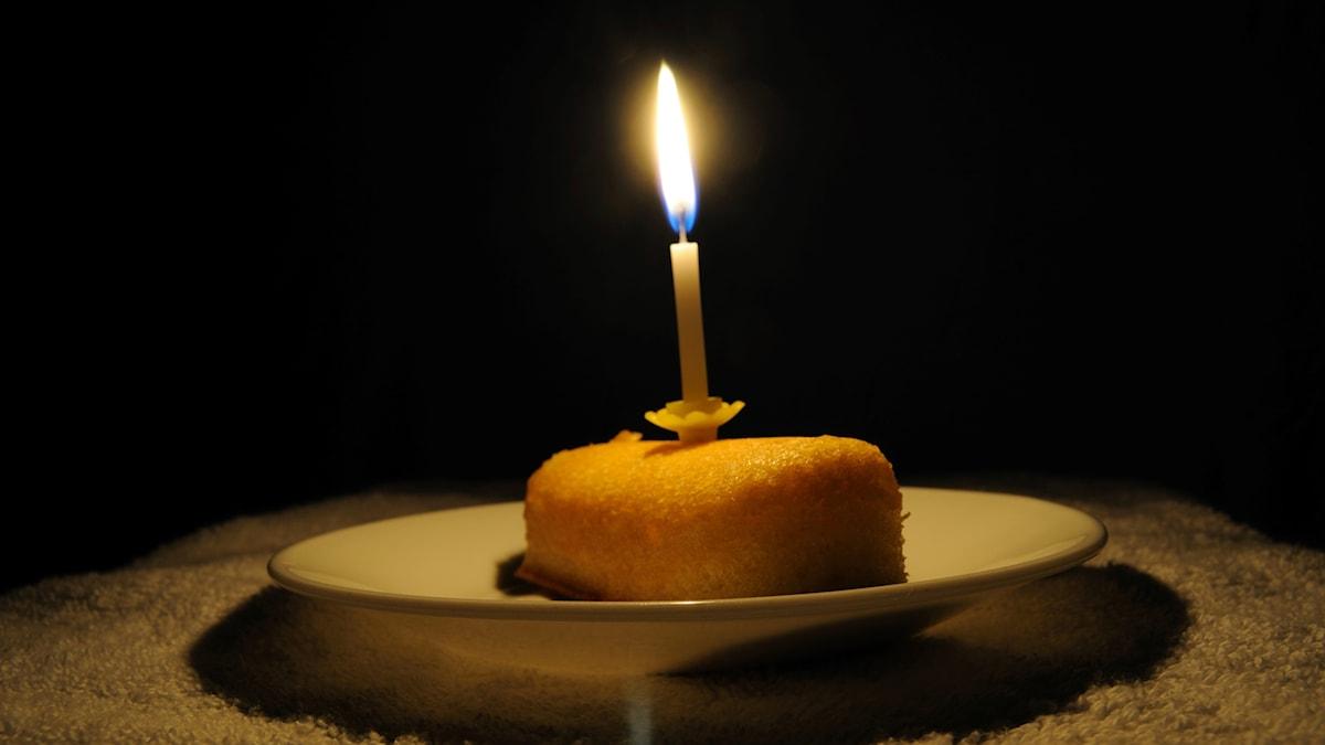 Bakverk med ett brinnande födelsedagsljus i, på tallrik.