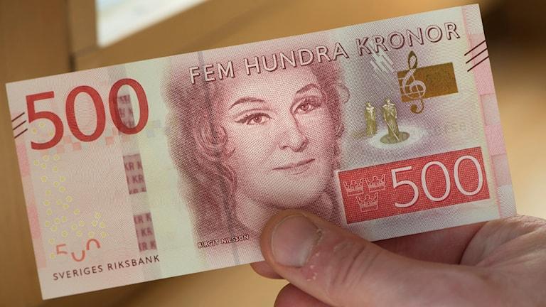 En hand håller i den nya femhundralappen med motivet Birgit Nilsson.