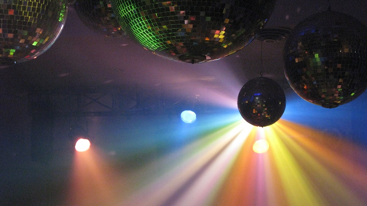 Färgglad belysning och spegelbollar i taket på ett disco.