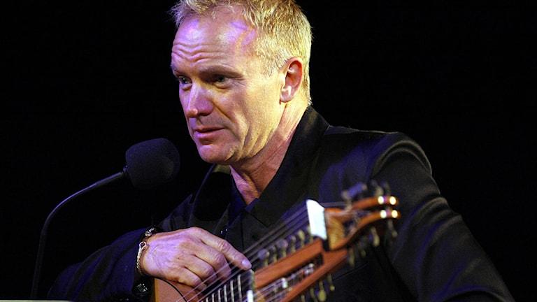 Sting sitter med sin luta framför en mikrofon.