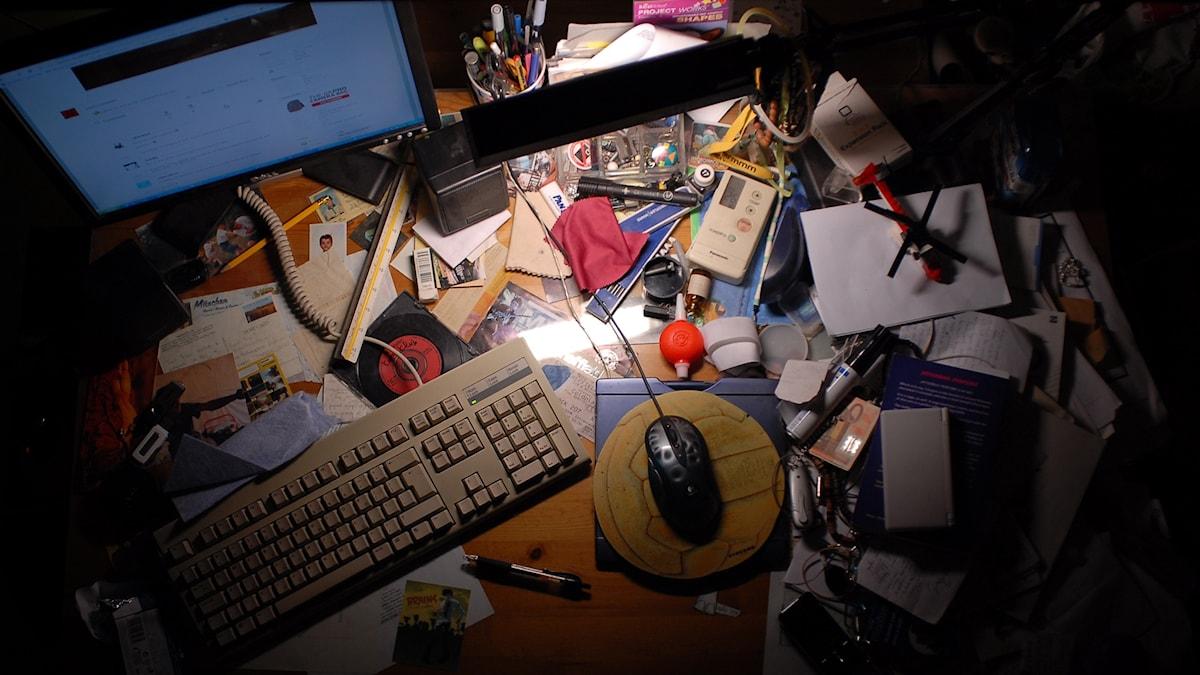 Ett rörigt skrivbord med massor av prylar överallt bland tangentbordet och datormusen.