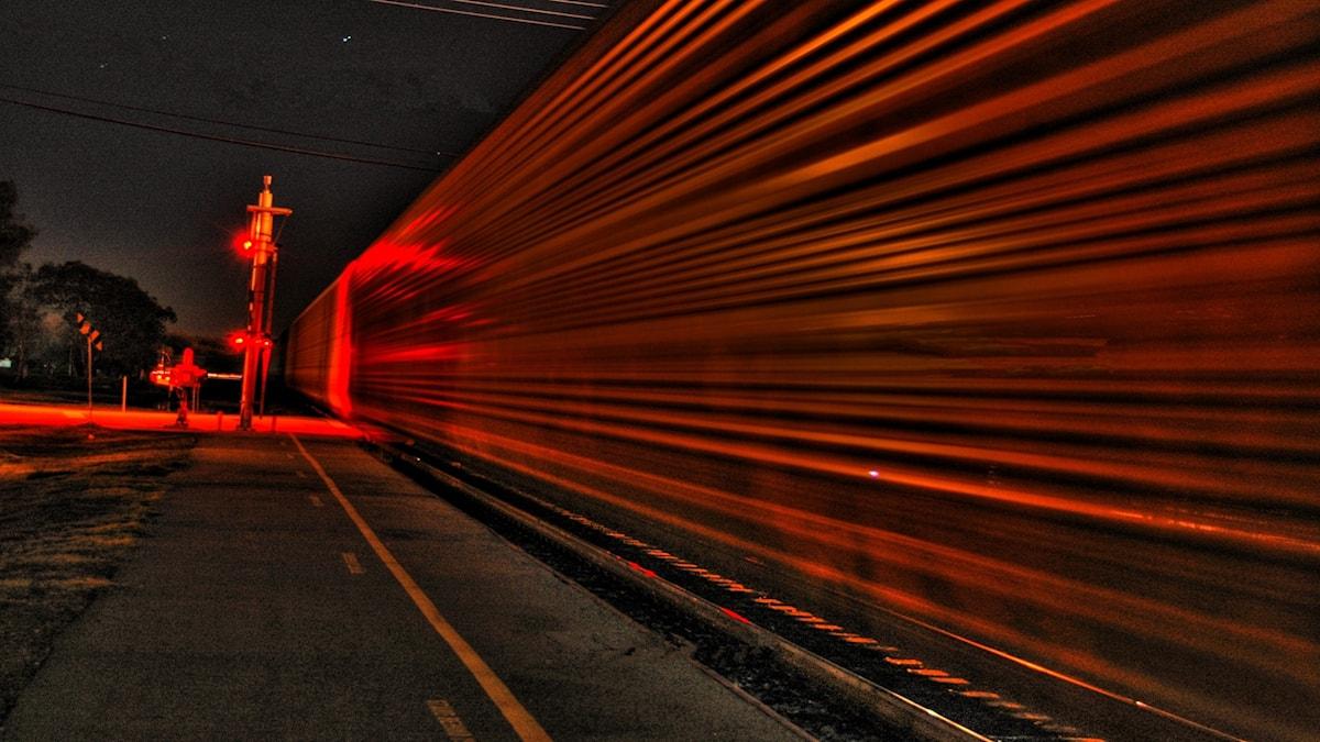 Nattåg som rusar fram vid en järnvägsövergång.