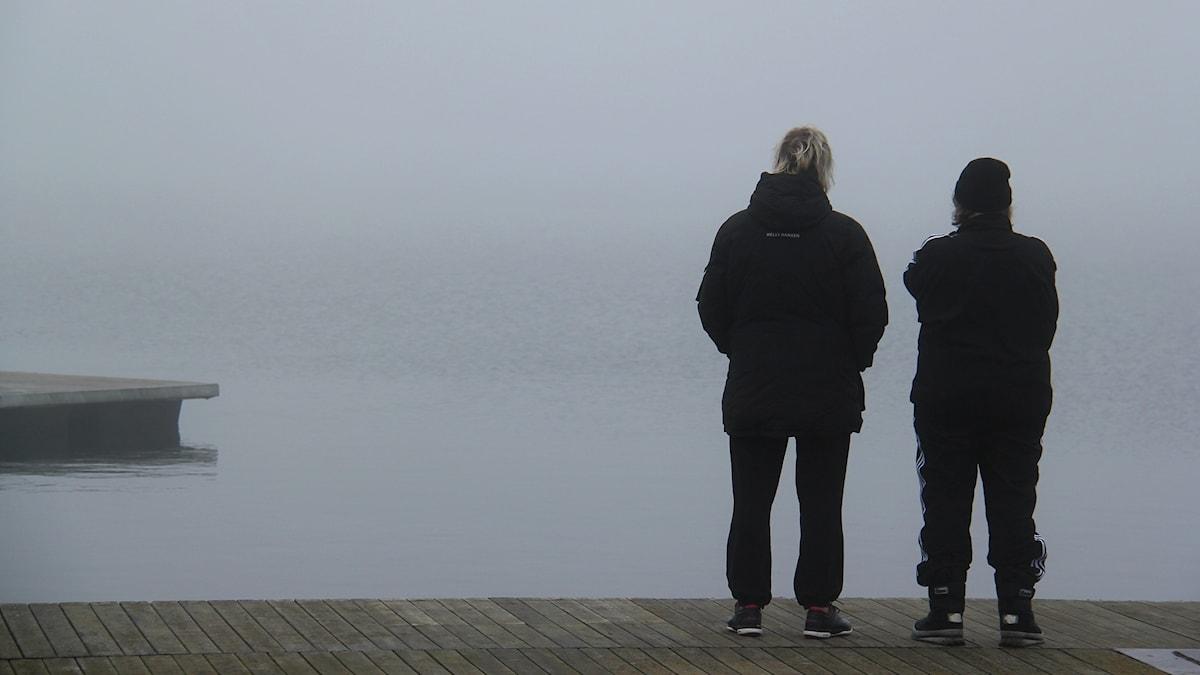 Två personer står på en kaj och tittar ut över ett dimtätt vatten.