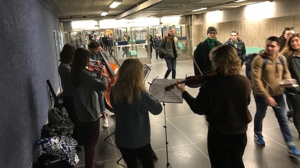 Emma Alrikson och hennes vänner spelar stråkinstrument i tunnelbanegången.