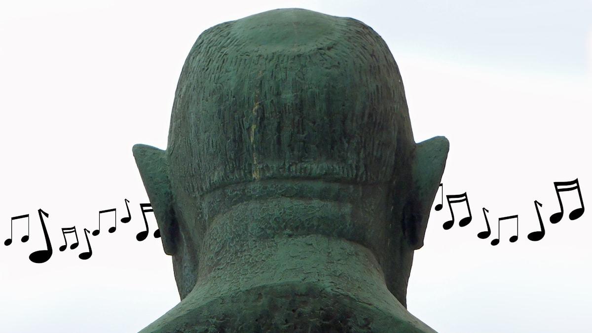 Bakhuvudet på en staty där man ser noter strömma in genom ena örat och ut genom det andra.