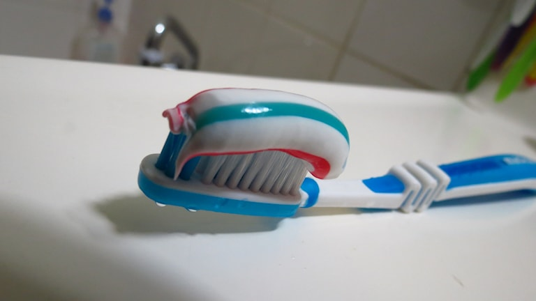 Tandborste med randig tandkräm ligger på kanten av ett handfat.