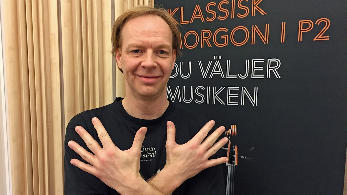 Pianisten Per Tengstrand håller upp sina båda händer och spärrar ut fingrarna.