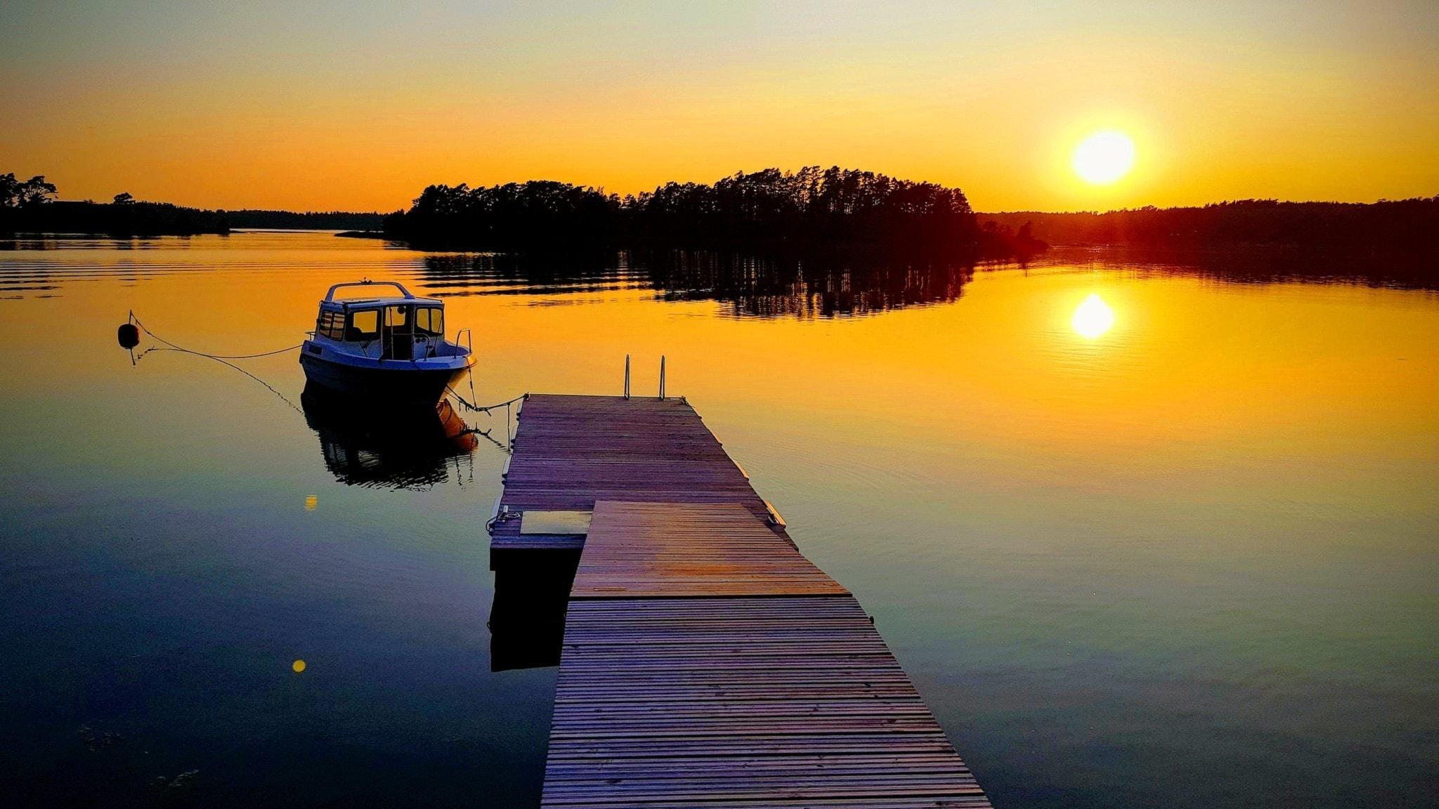 En brygga med en angjord båt i den finska skärgården där solen är på väg ner i horisonten en sen julikväll.