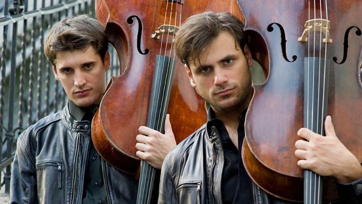 Cellisterna Luka Sulic och Stjepan Hauser i duon 2Cellos håller varsin cello över axeln.