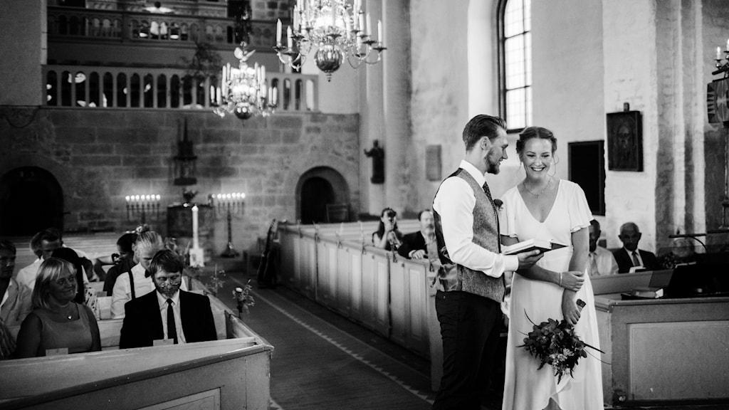 Ett bröllopspar som står längst fram i gången i en kyrka och det sitter lite folk i bänkarna.