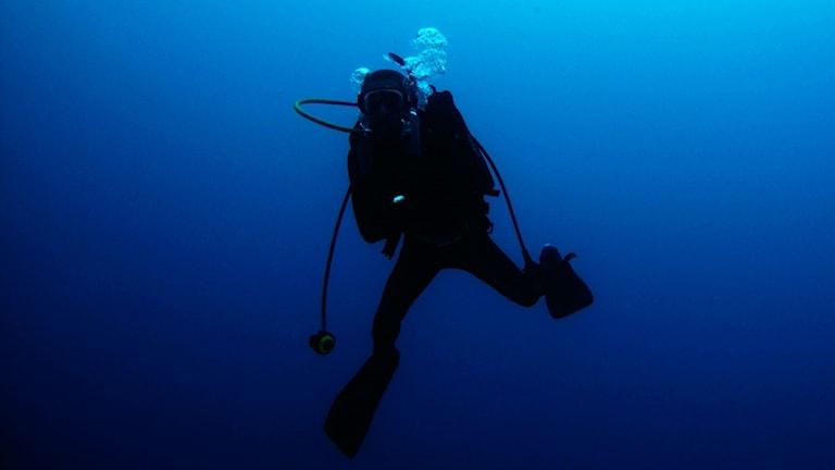 Siluetten av en dykare med utrustning under vattnet.