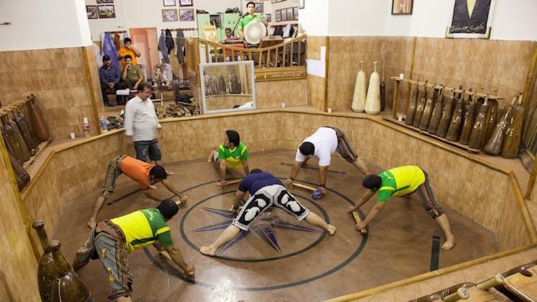 Män i ring som utövar den iranska rituella gymnastiken Zurkhaneh.