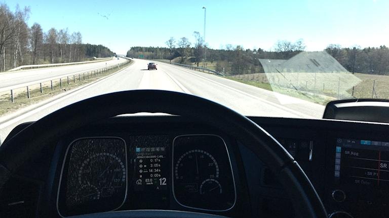 Utsikt genom vindrutan på en bil som färdas på en motorväg.
