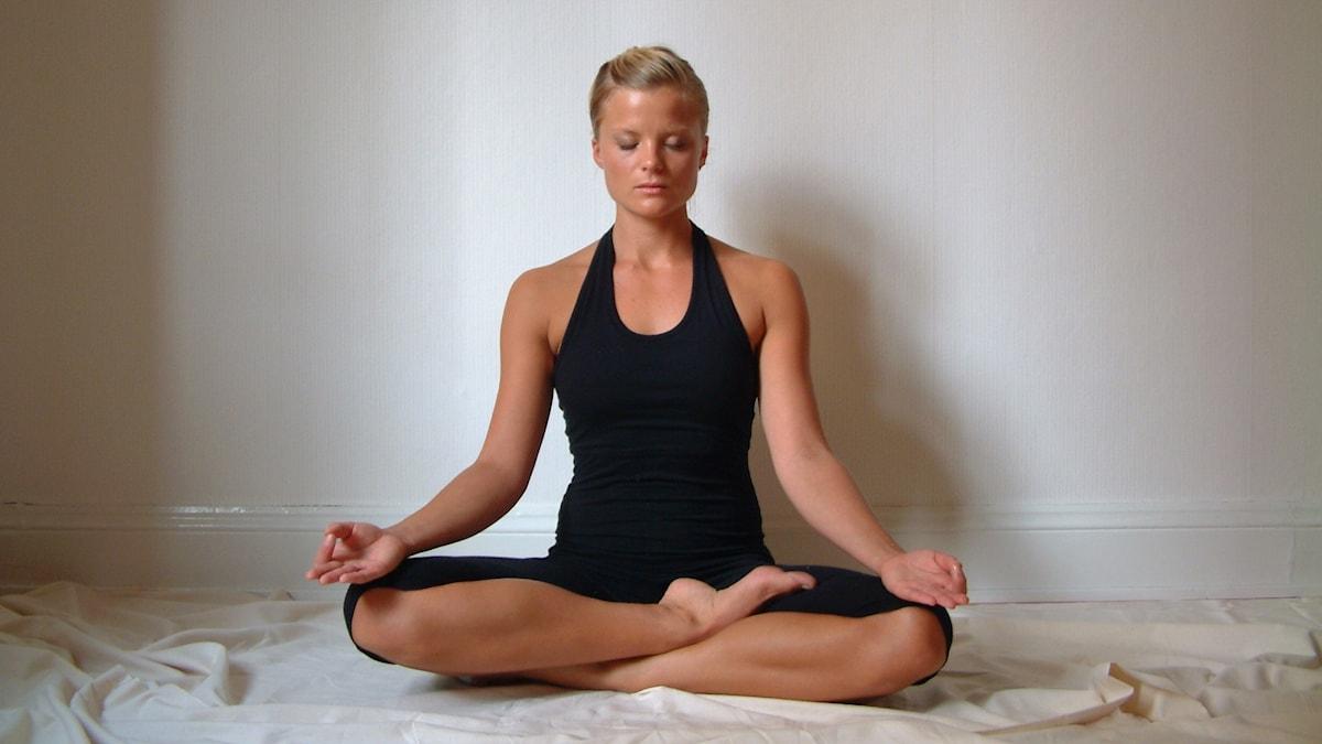 Ung kvinna som mediterar i lotusställning med händerna vilande på sina knän.