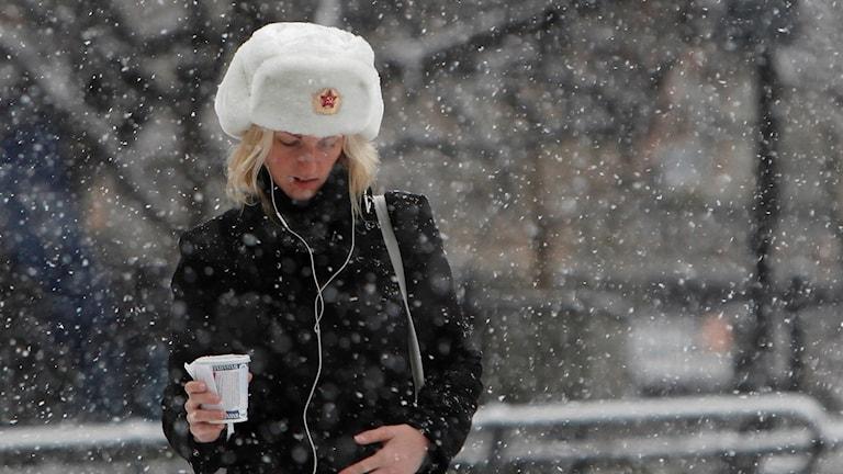 En ung kvinna med en takeaway-kaffe i handen går med en stor pälsmössa på huvudet i snöfallet och lyssnar på musik i sina hörlurar.