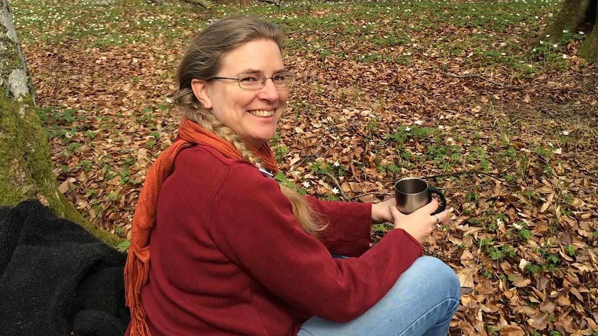 Pernilla Eskilsdotter sitter bland höstlöven med en kaffemugg i handen.