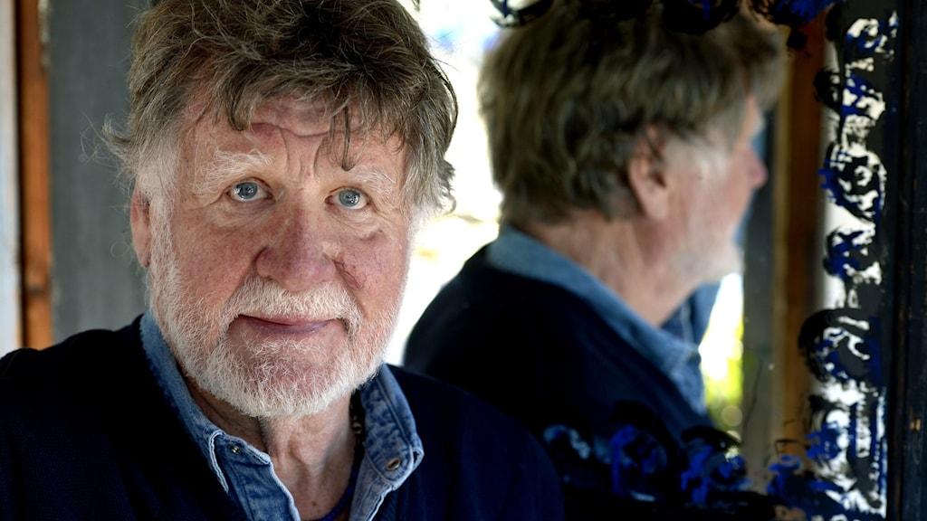 Musikern och vissångaren Carl Anton Axelsson framför en spegel där man ser hans profil avspeglas.