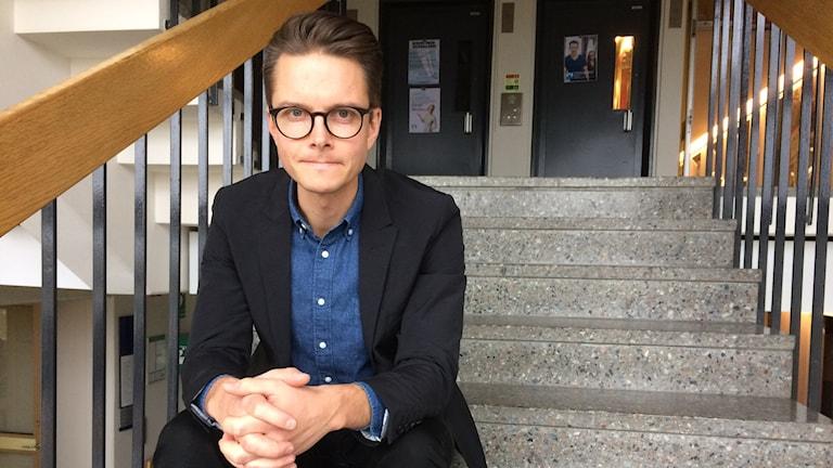 Karl-Oskar Freij sitter i en trappa i  Radiohuset i Stockholm.