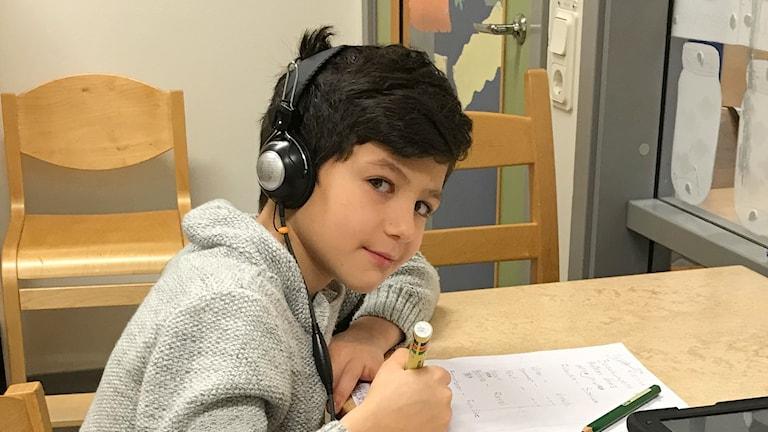 Jonas Ahmad sitter vid ett bord och skriver. Han har hörlurar på sig.